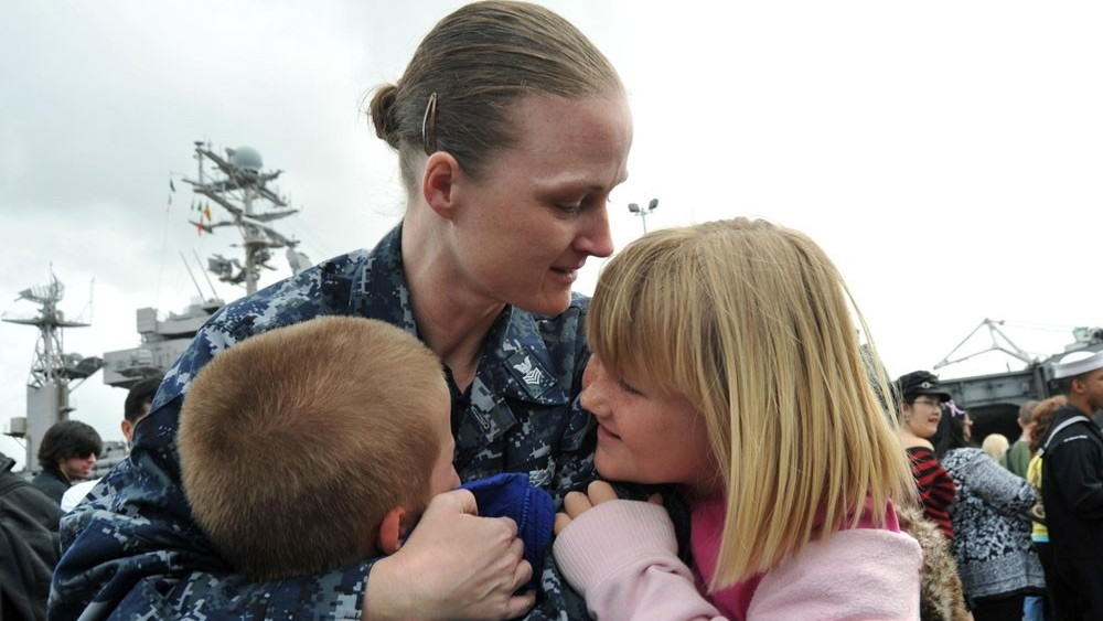 A woman dressed in military fatigues hugs two young children