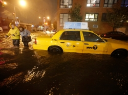 Pedestrians walk past a submerged taxi in Brooklyn, New York, during Hurricane Sandy last year.