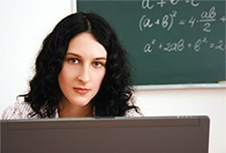 A female teacher is posed in front of a chalkboard with algebraic equations on it.