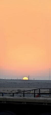 The sun rises in the distance as the last of the U.S. military convoys passes the Khabari Crossing from Iraq into Kuwait