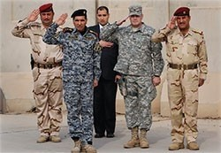 A member of the U.S. military and Iraqi Army officers salute during a ceremony signifying the end of U.S. presence in Iraq