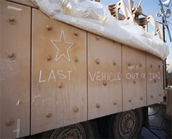 A message in chalk identifies the last armored vehicle out of Iraq