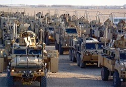 Armored vehicles accompanying the last convoy to leave Iraq arrive at Camp Virginia, Kuwait