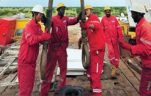 Chinese workers from Sinopec's Zhongyuan Petroleum Exploration Bureau and Sudanese workers drill an oil well.