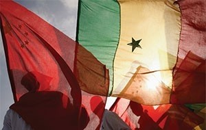 Men wave Chinese and Senegalese flags
