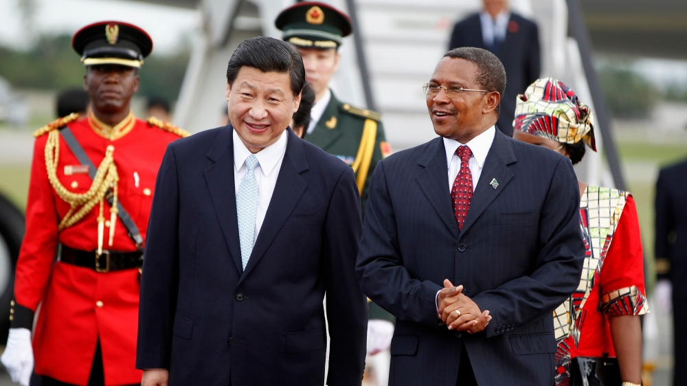 China's President Xi Jinping walks with his Tanzanian counterpart Jakaya Kikwete