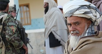 An Afghan man looks away as another Afghan man talks with soldiers in the background