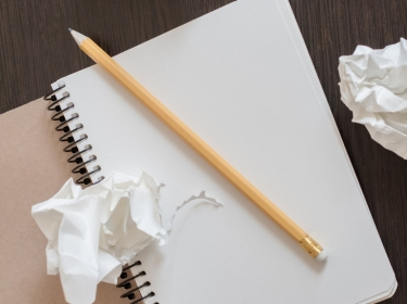 Pencil and notebook with crumpled paper
