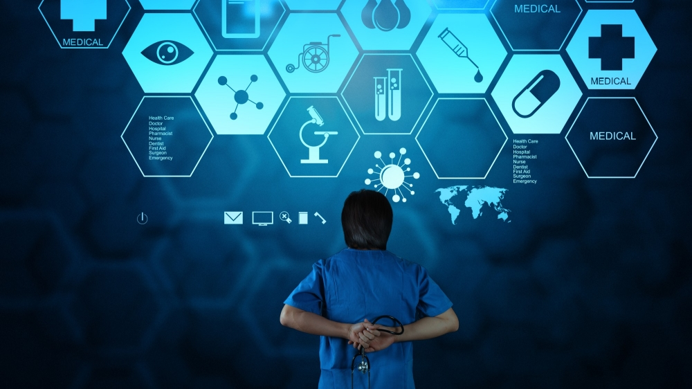 Doctor standing in front of abstract computer screen with icons