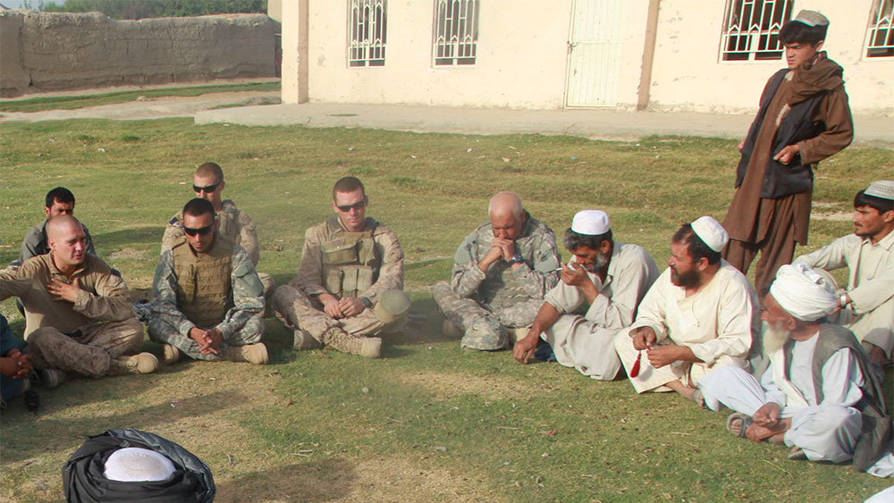 A group of soldiers and men dressed in Middle Eastern clothing sit in a circle.