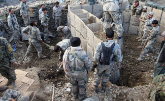 A group of soldiers create a barrier by filling square containers with dirt.