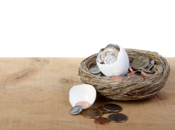 A cracked open egg with coins spilling out