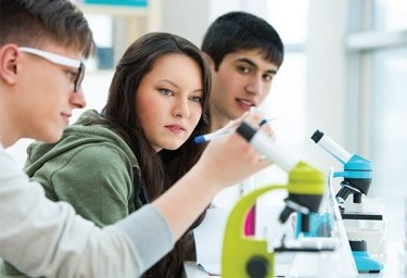 Three students in front of microscopes.