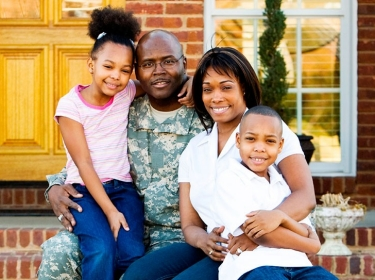 A miliatry family sits in front of their house