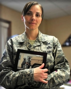 A female soldier holds a photo of another soldier