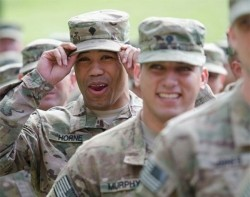 A soldier adjusts his hat