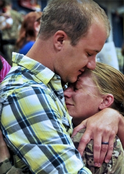 A man hugs a woman soldier