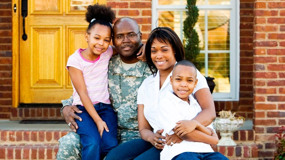 A military family sits in front of their house