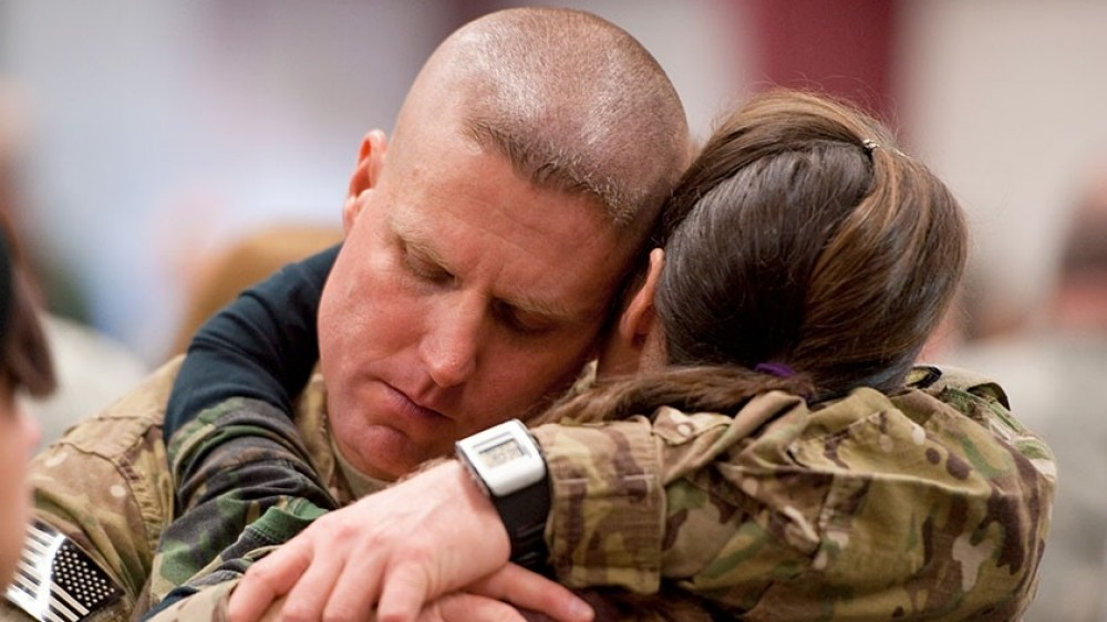 The face of a soldier as he hugs a woman.