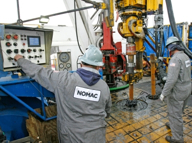Workers prepare to change drilling pipes on the rotary table of a natural