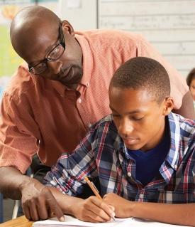 A teacher looks over a sudent's shoulder