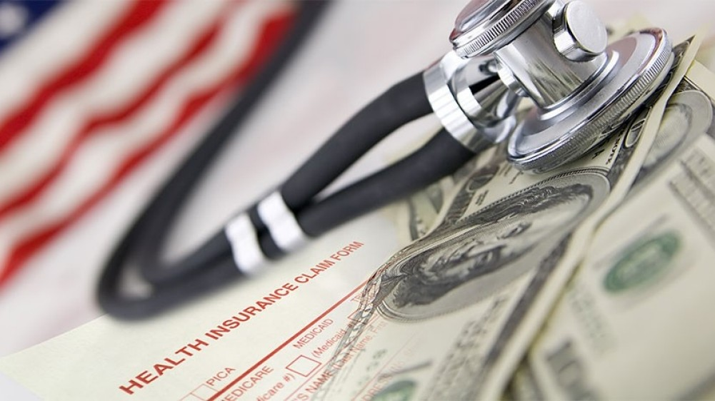 A stethoscope lies on top of cash and a health insurance claim form with the American flag in the background.