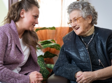 A young woman cares for her elderly grandmother
