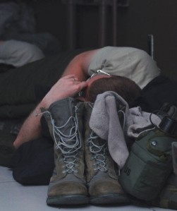 A soldier's boots sit close to his head while he sleeps.