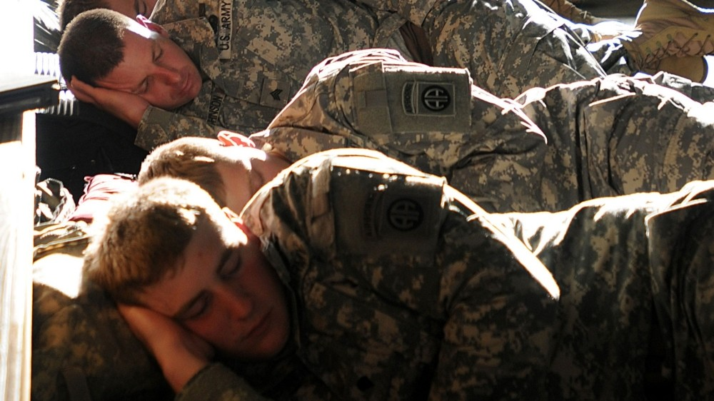 Soldiers try to sleep during the day