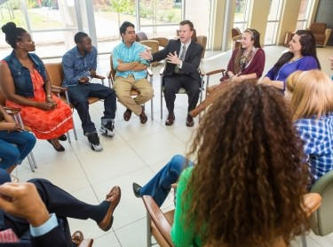 Man talking to a diverse group of people during a therapy session