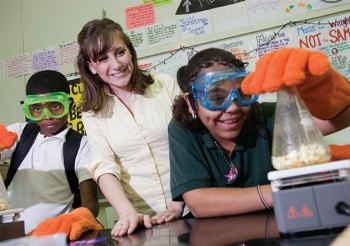 A student heads a beaker while a teacher looks on