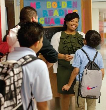 A teacher greets students