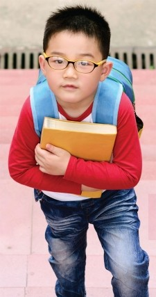 A boy with a blue backpack holds a book