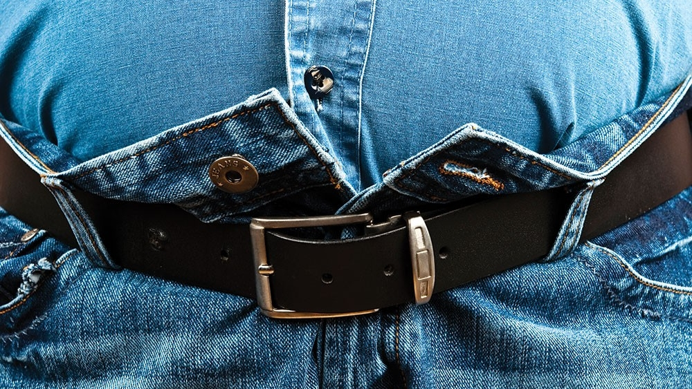 An expanding waist causes a belt to struggle to keep jeans together