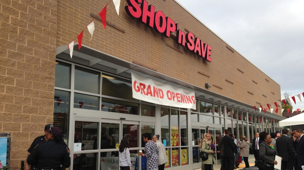 People gather outside the grand opening of a Shop 'n Save grocery store