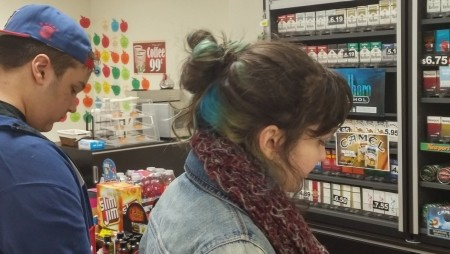 Two teenagers at a convenience store counter
