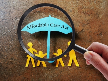 Paper family under a Affordable Care Act umbrella with magnifying glass