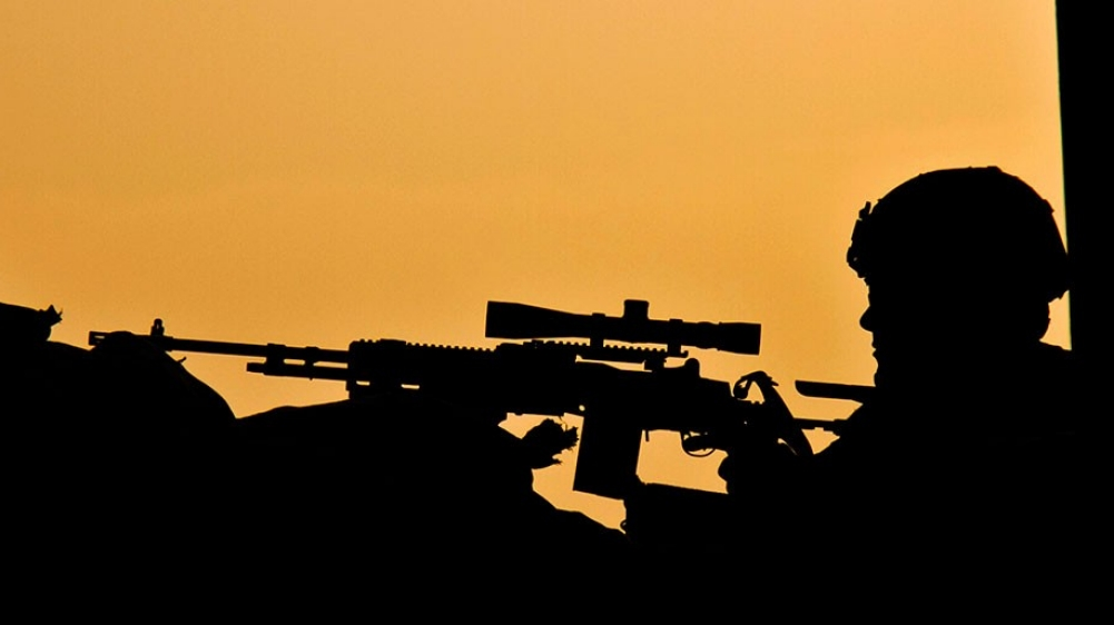 A silhouetted soldier conducts drills in front of an orange sky.