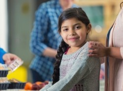 Hispanic girl in line at food bank kitchen