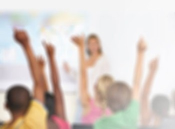 A teacher stands in front of a wall map while the students in front of her raise their hands