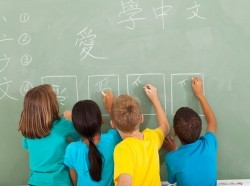 Elementary school students learning Chinese writing on chalkboard