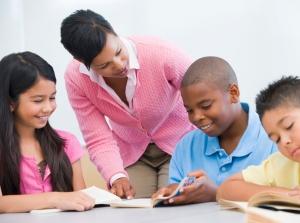 Teacher helping schoolboy.