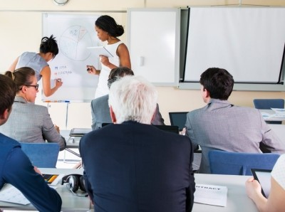 A group of people listen as two presenters write on a white board