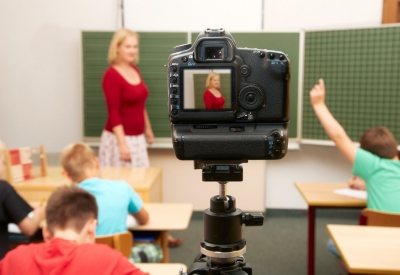 A camera takes pictures as a teacher speaks to her students