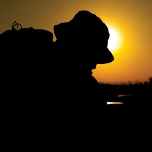 A silhouetted soldier begins a march as the sun rises