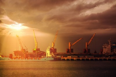 Orange sunlight shines through dark clouds over a collection of shipping cranes