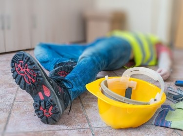 A worker lying injured on the ground