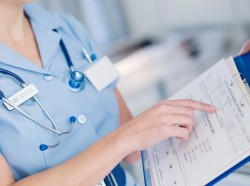 Close up of a nurse looking at a patient's medical chart