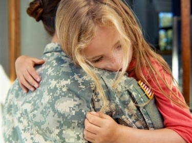 Female soldier hugging a child