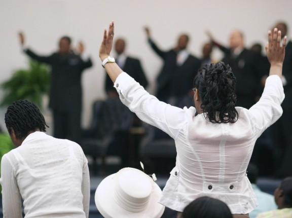 African American woman with hands raised in worship at a church service